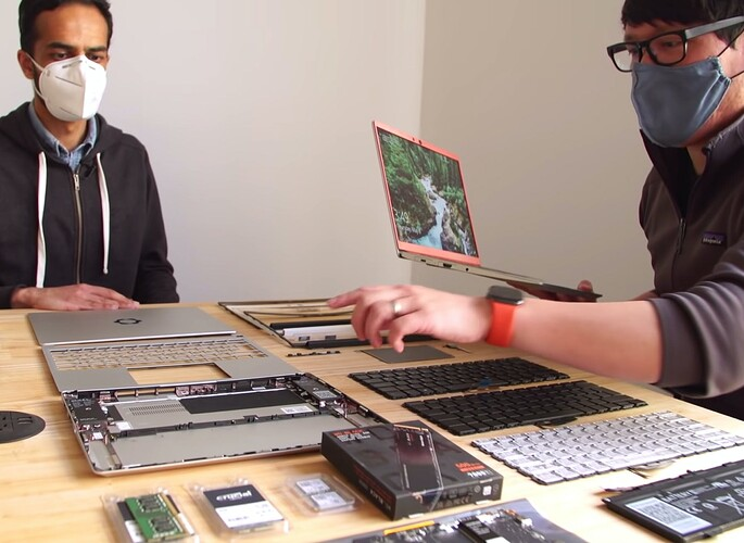 Two people gathered around a table of Framework Laptop parts