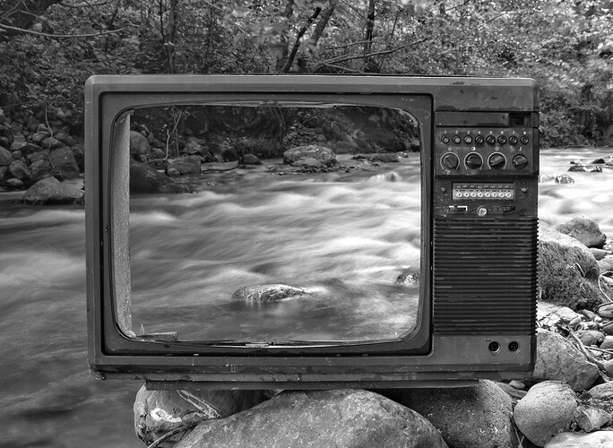 An empty TV screen in front of a creek